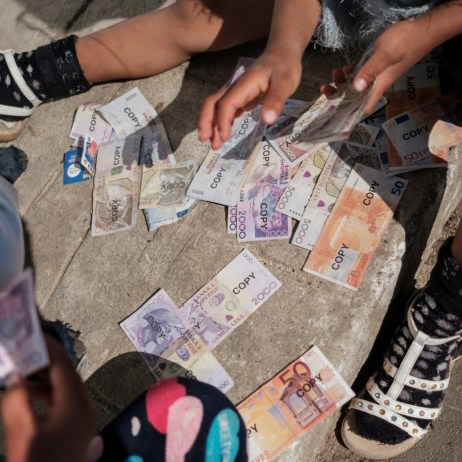 Some kids are playing with fake money on the sidewalk inside a Roma community settlement in Tirana, Albania 2019. © Matteo Bastianelli