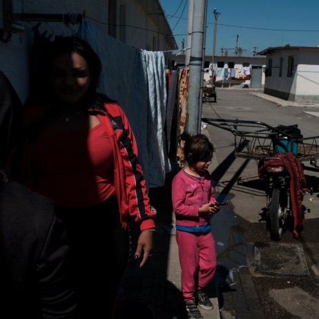 """40-year-old Orkida Driza is seen talking with other members of the Romani community living in the settlement, while some kids play around a motorcycle cart . Orkida was given in marriage at the tender age of 14 by her family, she's divorced now and has five children. She is currently the leader of the Roman Organization """"Catia e Gruas Rome"""", which stands for the rights of the Roma minorities in Tirana, Albania 2019. © Matteo Bastianelli"""