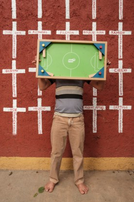 "A 10-year-old boy, who came from Honduras along with his parents, is seen portrayed while hiding his face with one of his favourite toys. Behind him, a wall painted with crosses reporting the names of migrants who found shelter in ""Casa del Buen Samaritano"" and, after starting their journey to the US border, they disappeared. Oaxaca de Juarez, Mexico 2019. © Matteo Bastianelli"