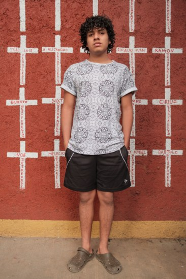 "20-year-old Marvin Gómez, who came from Honduras, is seen portrayed at the shelter of ""Casa del Buen Samaritano"". Behind him, a wall painted with crosses reporting the names of migrants who found shelter there and, after starting their journey to the US border, they disappeared. Nevertheless, Marvin hopes to get to the USA. Oaxaca de Juarez, Mexico 2019. © Matteo Bastianelli"
