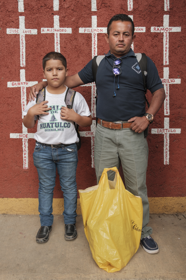 "32-year-old Adelfo Reyes and his 11-year-old son Astor Noe, who came from Colón, Honduras, are seen portrayed at the shelter of ""Casa del Buen Samaritano"". Behind them, a wall painted with crosses reporting the names of migrants who found shelter there and, after starting their journey to the US border, they disappeared. Adelfo and his son decided to return to Honduras because Astor's mother misses her son too much. Oaxaca de Juarez, Mexico 2019. © Matteo Bastianelli"