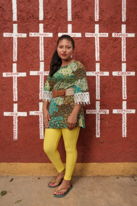 """19-year-old Cindy Janeth Flores Rodriguez, who came from San Pedro, Honduras, is seen portrayed at the shelter of """"Casa del Buen Samaritano"""". Behind her, a wall painted with crosses reporting the names of migrants who found shelter there and, after starting their journey to the US border, they disappeared. Cindy left Honduras on August 2019 and has now applied for asylum in Mexico. Oaxaca de Juarez, Mexico 2019. © Matteo Bastianelli"""