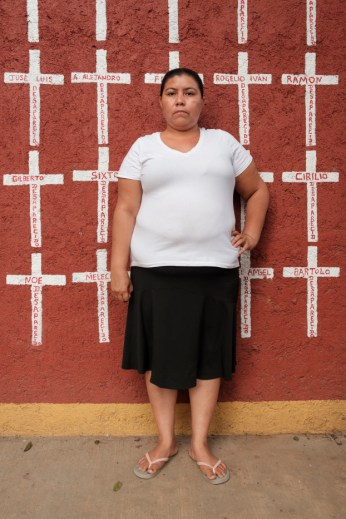 """41-year-old Lorena Paguaga, who came from Villanueva Cortés, Honduras, is seen portrayed at the shelter of """"Casa del Buen Samaritano"""". Behind her, a wall painted with crosses reporting the names of migrants who found shelter there and, after starting their journey to the US border, they disappeared. Lorena left Honduras for safety reasons and is looking for a safer place for her children to live. Oaxaca de Juarez, Mexico 2019. © Matteo Bastianelli"""