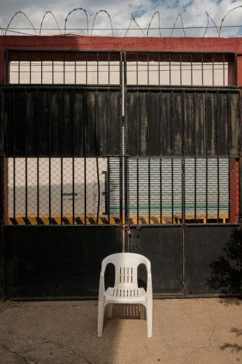 "An empty chair in front of the entrance gate of ""Casa del Buen Samaritano"", run by the Migrant Orientation Center of Oaxaca (COMI), a nonprofit organization that provides humanitarian assistance to migrants. Oaxaca de Juarez, Mexico 2019. © Matteo Bastianelli"