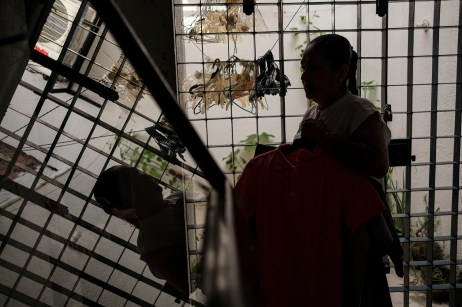 "54-year-old Maria Emma Mora Liberato is seen inside her house, holding in the hands some of her son's clothes. Jose Alberto Telles Mora disappeared on 20 September 2011 at the age of 14 years old. After 8 years, Emma was not yet able to find her son and she is now the president of the NGO ""Familias de Acapulco en busca de sus desaparecidos"", a civil organization that helps other families to find their beloved ones. Supported by an international project promoted by the AVSI foundation and financed by the EU, local NGOs are trying to change their future. Acapulco, Mexico 2019. © Matteo Bastianelli"