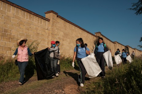 A group of students of professional career in community health at CONALEP, are seen with gloves and trash bags, cleaning the area around the local river from plastic waste with the help of their teachers. Santiago Huajolotitlán, Mexico 2019. © Matteo Bastianelli