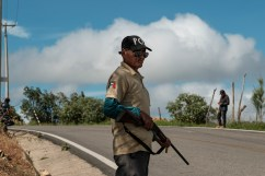 "A man is seen armed with a rifle in La Montaña region. The local indigenous community feels abandoned and not protected by the State of Guerrero, the second-poorest and most violent state in the country, therefore in 2012 they created the ""Policia Ciudadana y Popular"", an organization, not recognized by the authority, that try to prevent violence and criminal activities patrolling the roads and monitoring the vehicles in transit to ensure people are able to move safely in the area. Temalacatzingo, Mexico 2019. © Matteo Bastianelli"