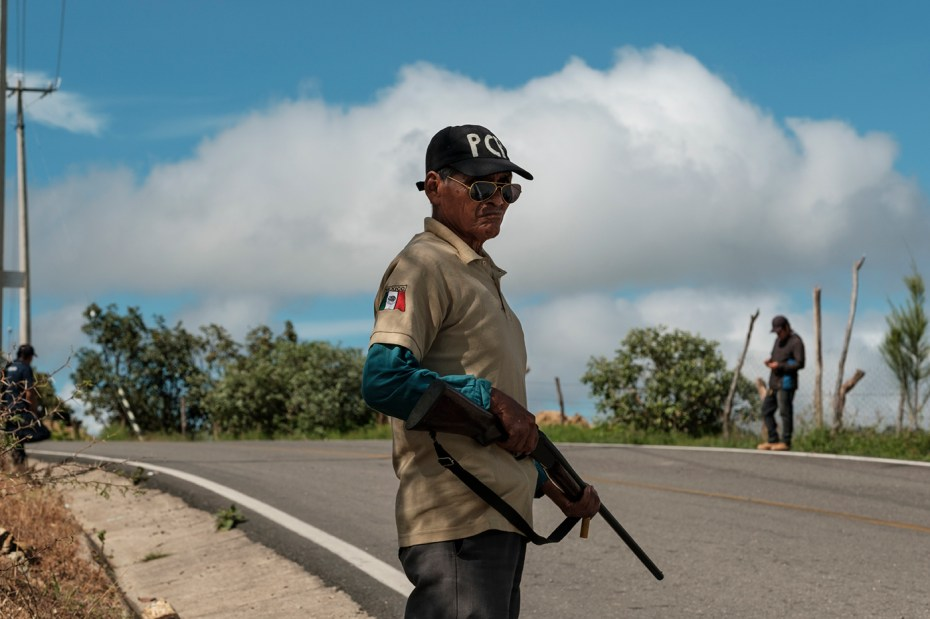 """A man is seen armed with a rifle in La Montaña region. The local indigenous community feels abandoned and not protected by the State of Guerrero, the second-poorest and most violent state in the country, therefore in 2012 they created the """"Policia Ciudadana y Popular"""", an organization, not recognized by the authority, that try to prevent violence and criminal activities patrolling the roads and monitoring the vehicles in transit to ensure people are able to move safely in the area. Temalacatzingo, Mexico 2019. © Matteo Bastianelli"""