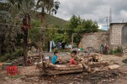 Louis Antonio and Felipe play on a tree log in the vicinity of their father's mechanic shop in the village of Santiago Nopala, Mexico 2019. © Matteo Bastianelli