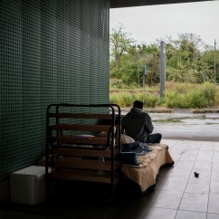 Cristian, a 26-year-old Nigerian migrant, is seen seated on his bed in a makeshift shelter at the Roma Tiburtina railway station. Hundreds of migrants are forced to live on the streets during Italy's lockdown aimed at stopping the spread of coronavirus. Rome, Italy, April 2020. © Matteo Bastianelli/National Geographic Society Covid-19 Emergency Fund