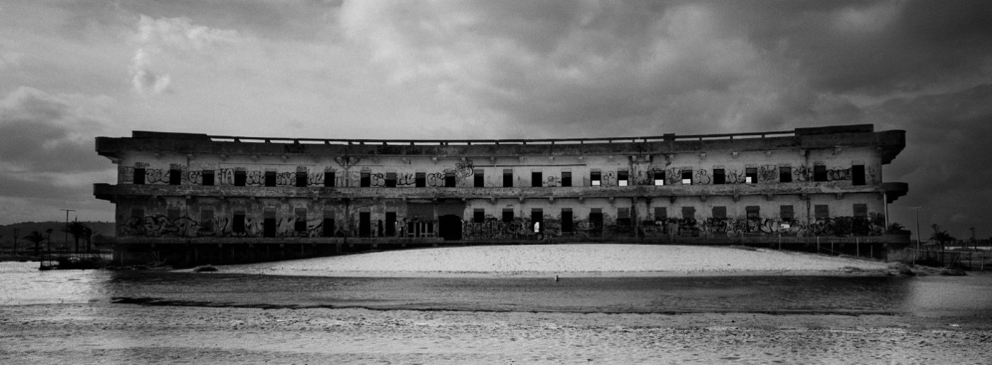 """A building dating back to the Fascist dictatorship on the Poetto beach, near the Molentargius-Saline Regional Park. Initially, it was built as a summer holiday camp, then it was converted into the """"Marino Hospital"""" and ultimately abandoned; the building is scheduled to be turned into a hotel. Cagliari, Italia 2015. © Matteo Bastianelli"""