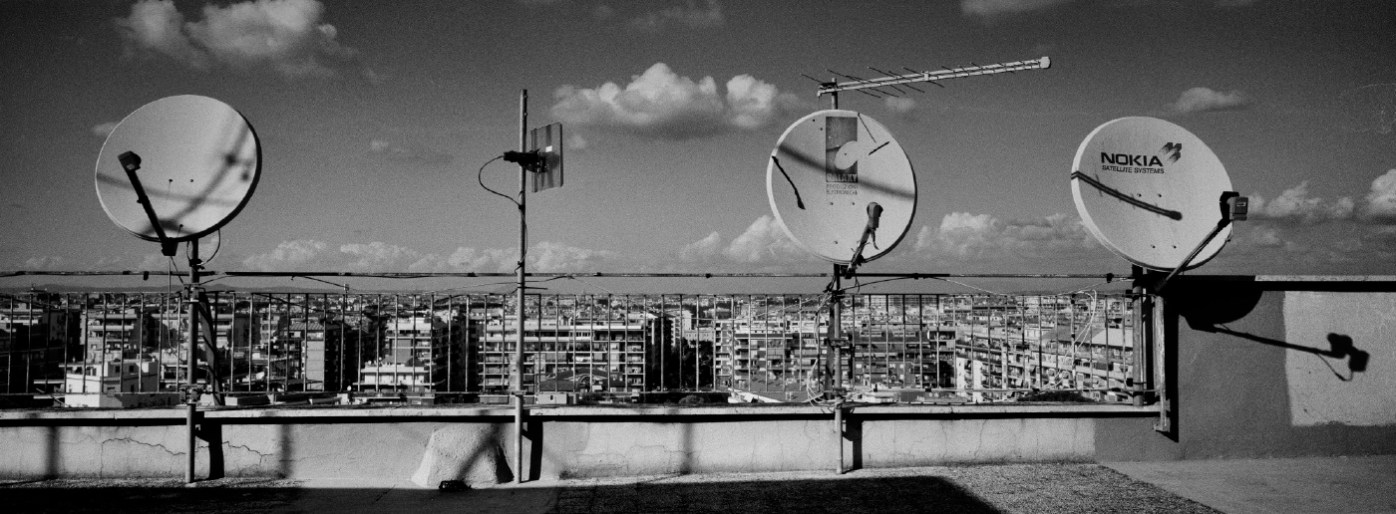 Some satellite dishes on a rooftop, in the background a view of the outskirts of Rome, Italy 2015. © Matteo Bastianelli
