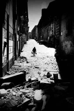 A woman wanders alone in the 'ghost-town' of the historical centre a few days after the earthquake. L'Aquila, Italy 2009. © Matteo Bastianelli