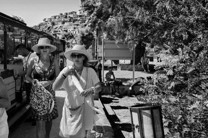 Two women just got off a touristic miniature train, are walking on a street of the city center while a group of refugees take a rest before resuming their journey towards Mytilene. Molyvos, Lesbos, Greece 2015. © Matteo Bastianelli
