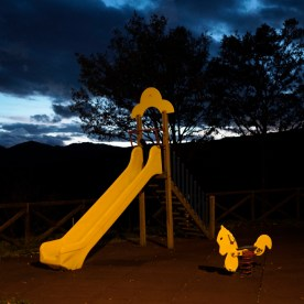 A children's playground in the vicinity of dozens of earthquake-proof wooden houses built after the earthquake of 1997 and left empty or almost unused. Forcella (Serravalle del Chienti), Italy 2016. © Matteo Bastianelli