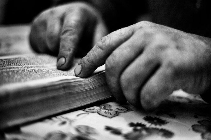 Ettore Boccuni, 48 yr old fisherman from Taranto, reading the Sacred Scriptures. He has been studying the Bible for a year but, contrary to most of his fellow citizens, doesn't take part in Holy Week. Taranto, Italy 2013. © Matteo Bastianelli