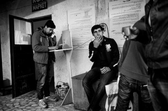 20-year-old Syrian refugee Mohamad Al Masalmeh is trying to phone his family in Syria, while his friend Omran Alhariri, 26 years old, is drinking coffee in the refugee camp where they lived for one year. Harmanli, Bulgaria 2014. © Matteo Bastianelli