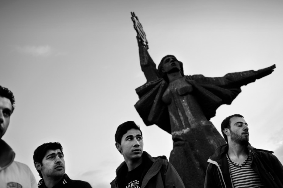 20-year-old Syrian refugee Mohamad Al Masalmeh is seen under the Statue of Europe with his cousins Hany (23) and Mohamad (29) and his friend Omran (26). The statue of Europe, located at the entrance of the city, represents a woman holding the sign of Europe in her raised hand, while the left seems to notice the alt. Harmanli, Bulgaria 2014. © Matteo Bastianelli
