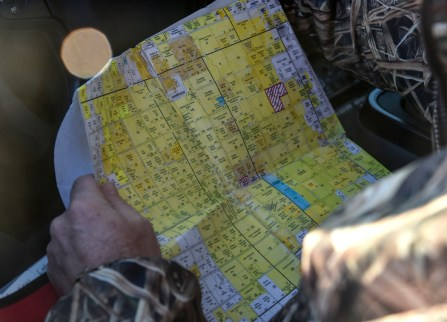 Brad Baumgartner, GF&P wildlife damage specialist, checks his map of potential plots of where to search for coyotes out in his truck in a field east of Howard on Thursday morning. (Matt Gade/Republic)