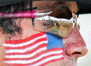 Wade Leusink, of Maurice Iowa, is seen in the reflection of the rodeo clown competing in the bull riding competition on the Saturday, June 4 in Crooks. (Matt Gade/Republic)