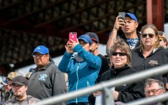 Spectators watch the back end as the horses run the back stretch of the eighth race during the Pari-Mutual Horse Races at the Brown County Fairgrounds on Sunday in Aberdeen.