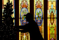 David Rohs, of Lyons, is seen in silhouette against the stained glass windows in the chapel as he assembles an artificial tree for advent at First Presbyterian Church of Boulder on Thursday. Go to dailycamera.com for more photos. Matthew Jonas / Staff Photographer Dec. 3, 2015