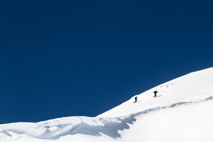 two snowboarders hike a ridge of fresh snow on a blue sky day looking for fresh tracks