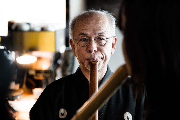 a flute master playing his flute in a small intimate performance in niseko