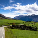 the road from wanaka to haast passes through green fields and vast mountains