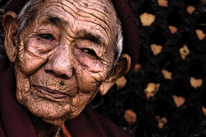 an elderly monk offers a peaceful smile towards all tourists visiting a temple in kathmandu
