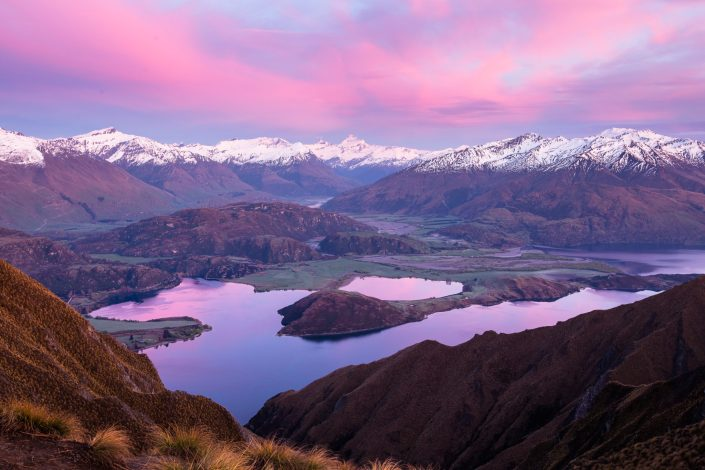 Dawn light creates pink clouds above the snowcapped mountain of wanaka