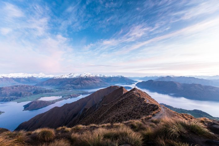 the sun rises over a snowcapped mountain range that looks out over lake wanaka in new zealand