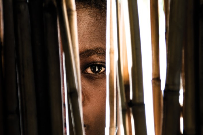 a young african boy looks through a bamboo fence into the lense of the photographer