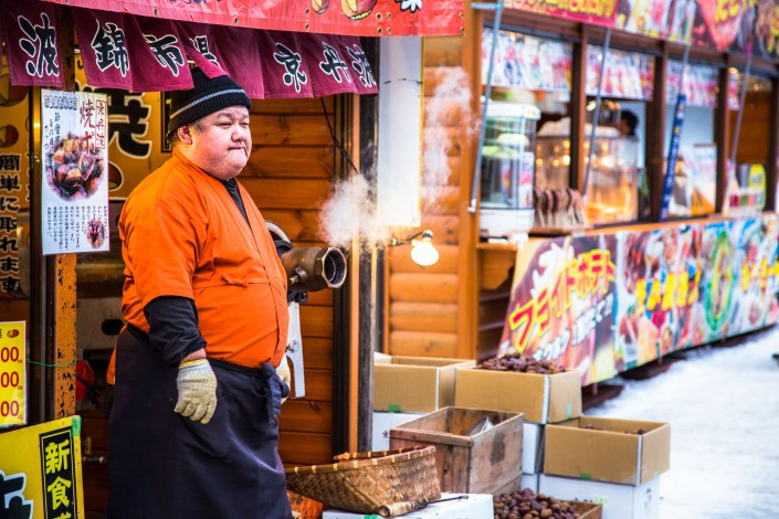 a man stands by his nut roasting machine at a local market in sapporo