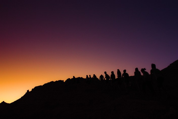 a group of hikers walk along a ridge as the sun sets in Chile