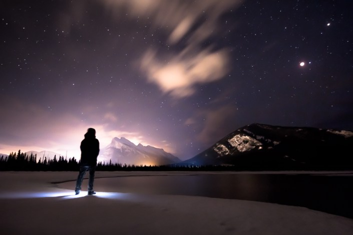 a self portrait under the stars and a red moon next to a frozen lake