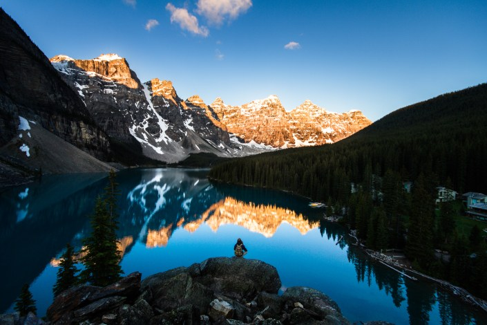 the morning sun illuminates the 10 peaks that surround Moraine lakes blue waters