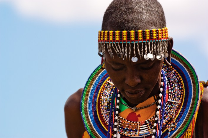 a portrait of a colourfully dressed maasai woman looks down while performing a welcome dance