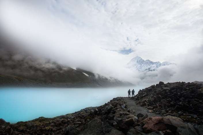 two hikers are on the edge of a blue lake in New Zealand's alpine