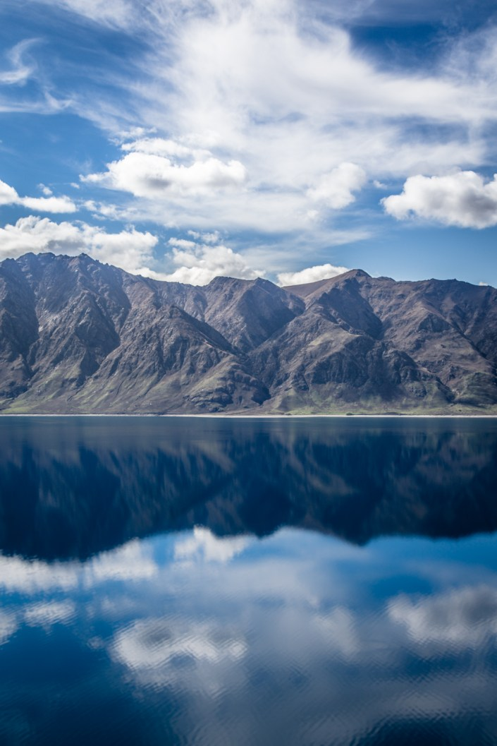 a lake with mirrored reflections of the mountains on the opposite bank