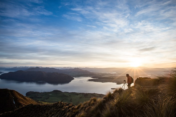 An man taking photographs on roys peak at sunrise looking out over mountains