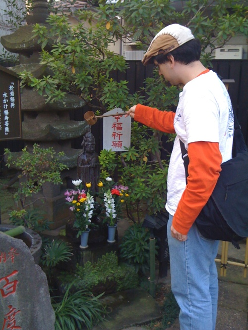 Pouring water to pray at Oiwa's shrine