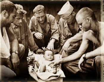 27th Infantry Division. Saipan, July, 1944. 'An abandoned Japanese baby is adopted by front line medical unit of the 27th Div. The baby was found with a scalp wound, in the arms of its dead mother,by a tank crew during the fighting below Mt. Tapotchau.' Courtesy New York State Military Museum.