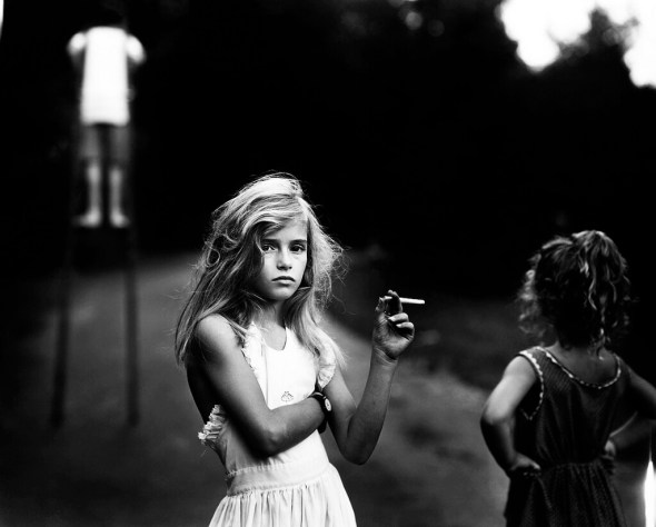 Sally Mann. This is a great example of a relatively wide open to medium aperture, for the depth of field is narrow. The girl with the cigarette is precisely defined and radiantly exposed, while the information in the foreground and background is relatively blurry. Because we know Sally Mann uses a large format view camera on a tripod, it is difficult to determine the exact shutter speed. However, it was obviously fast enough to stop the motion of the boy on stilts!