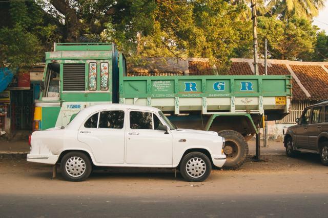 A white Hindustan Ambassador with a Green truck