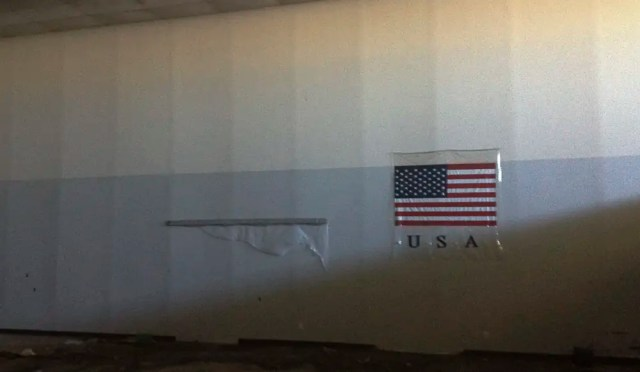 A plastic American flag hung on a huge empty wall