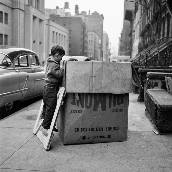 Boy looking into a cardboard box in New York City by Vivian Maier