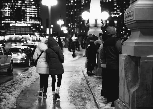 Two women walking on a snowy sidewalk in Chicago