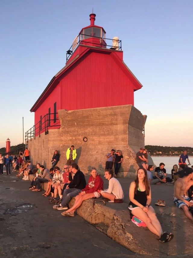 People enjoying the view and weather of on the Grand Haven Lighthouse