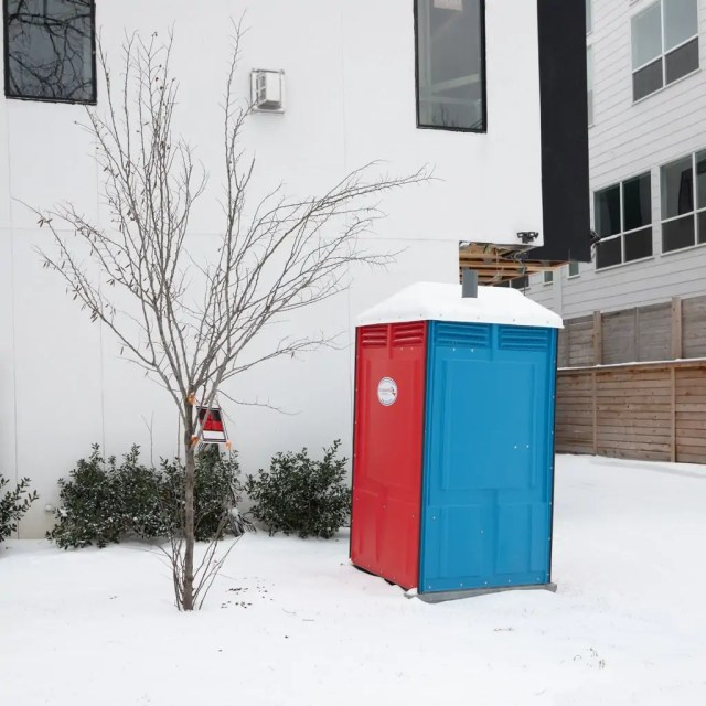 A colorful porta potty in the snow